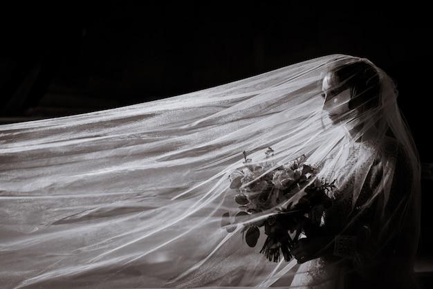 Vista lateral da foto em preto e branco da noiva com um buquê nas mãos e um longo véu