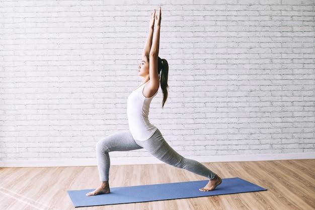 Vista lateral da garota apta praticando ioga, fazendo uma pose de guerreiro no tatame