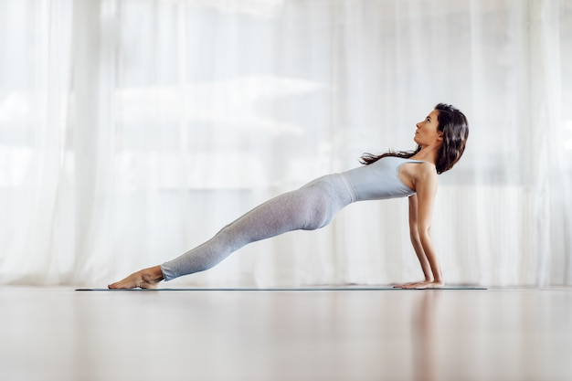 Vista lateral da garota magro e flexível com cabelo comprido na posição de ioga upward plank. interior do estúdio de ioga.