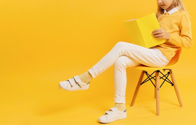 Vista lateral da garota posando ao ler o livro