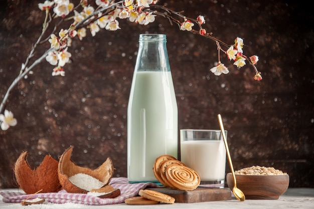 Vista lateral da garrafa de vidro aberta e do copo cheio de biscoitos de colher de leite e aveia em uma panela marrom na toalha roxa despojada na tábua de madeira