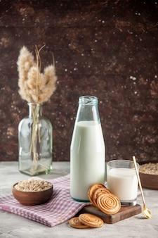 Vista lateral da garrafa de vidro aberta e do copo cheio de biscoitos de leite e aveia em uma panela marrom na toalha roxa despojada na tábua de madeira