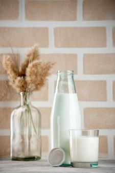 Vista lateral da garrafa de vidro e do copo com tampa de leite no fundo de tijolos de cor pastel