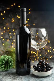 Vista lateral da garrafa de vinho tinto para a celebração de um copo vazio e uma casquinha de uva preta em fundo escuro