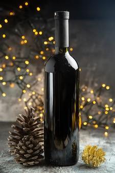 Vista lateral da garrafa de vinho tinto para celebração e dois cones de coníferas em fundo escuro