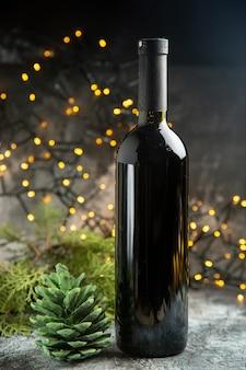 Vista lateral da garrafa de vinho tinto para celebração e um cone de conífera verde em fundo escuro