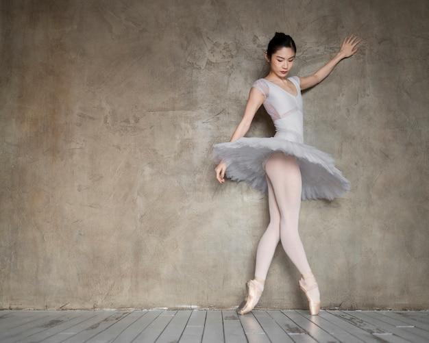 Vista lateral da graciosa bailarina com vestido de tutu com espaço de cópia