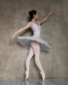 Vista lateral da graciosa bailarina com vestido de tutu