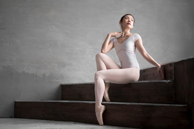 Vista lateral da graciosa bailarina posando nas escadas