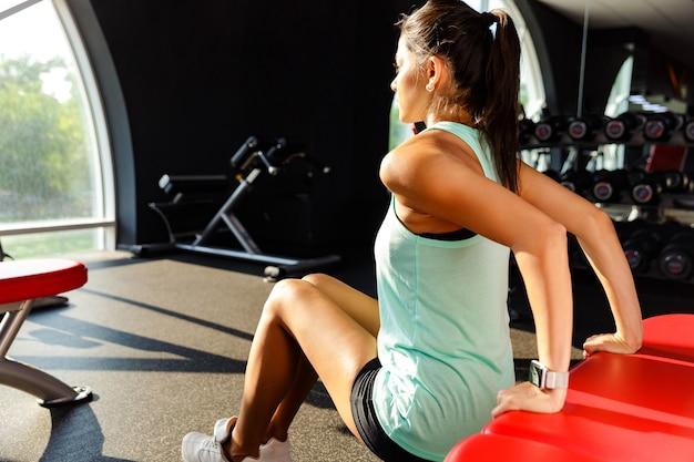 Vista lateral da incrível desportista fazendo exercícios de fitness no ginásio