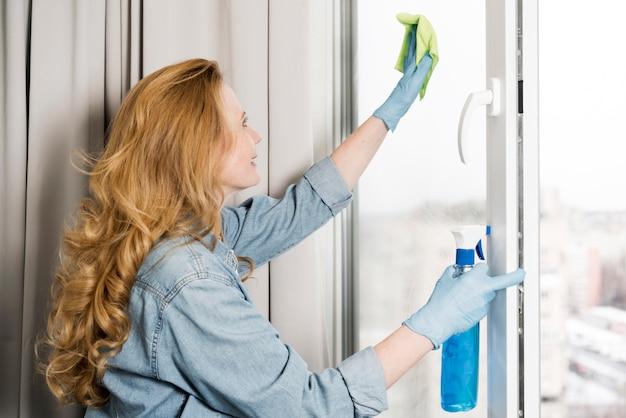 Vista lateral da janela de limpeza de mulher