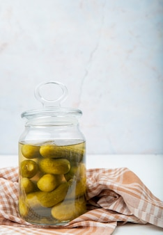 Vista lateral da jarra cheia de pepinos salgados no pano na superfície branca