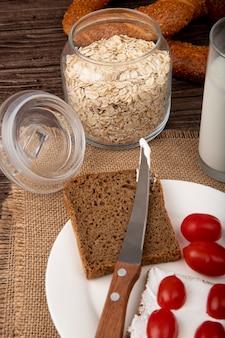 Vista lateral da jarra com flocos de aveia e prato com faca de tomate fatia pão de centeio de saco em fundo de madeira