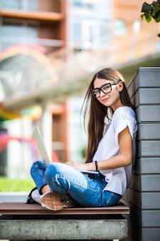 Vista lateral da jovem de óculos, sentado no banco do parque e usando o computador portátil