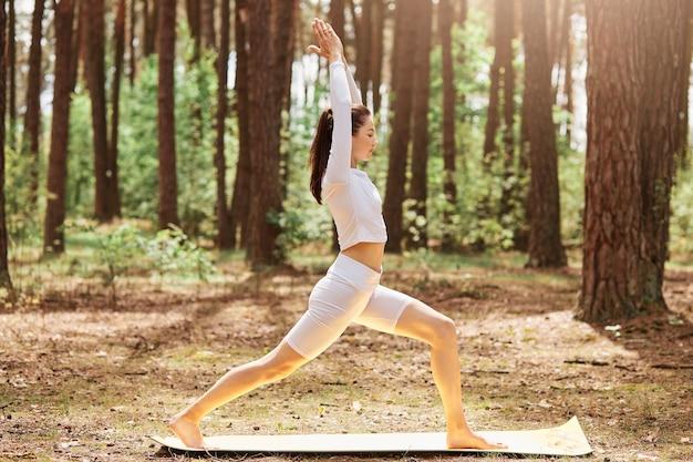 Vista lateral da jovem desportista adulta com corpo perfeito, vestidos elegantes top e leggins em pé em posição de ioga na floresta, relaxando em um dia ensolarado ao ar livre.
