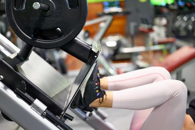 Vista lateral da jovem desportista em forma flexionando os músculos da perna na máquina de exercícios no ginásio.