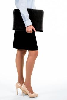 Vista lateral da jovem empresária. mulher segurando a caixa preta do tablet. hora de ir ao trabalho. a aparência é importante para os negócios.