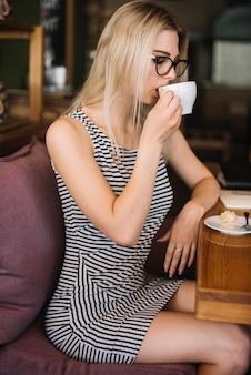 Vista lateral da jovem loira bebendo café no café
