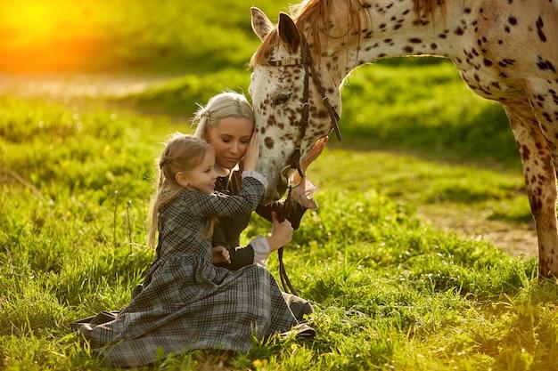 Vista lateral da jovem mãe com menina em vestidos abraçando cavalo irregular no prado verde.,