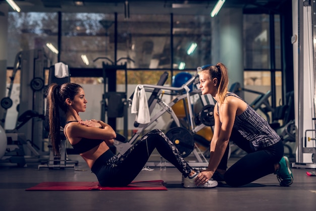 Vista lateral da jovem motivada atraente forma desportiva saudável saudável fazendo exercícios abdominais