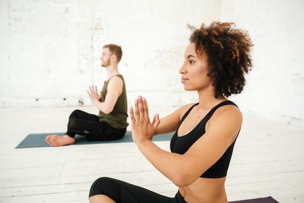 Vista lateral da jovem mulher africana fazendo yoga