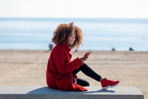 Vista lateral da jovem mulher afro-americana encaracolada bonita sentada em um banco na praia enquanto estiver usando um telefone celular ao ar livre