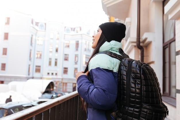 Vista lateral da jovem mulher asiática em roupas quentes