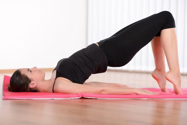Vista lateral da jovem mulher atrativa que treina na esteira da ioga.