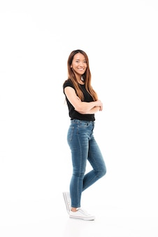 Vista lateral da jovem mulher bonita chinesa em camiseta preta e calça jeans em pé com as mãos cruzadas, olhando para a câmera