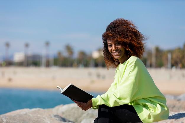 Vista lateral da jovem mulher encaracolada afro, sentado em um quebra-mar, segurando um livro enquanto sorrindo e olhando a câmera ao ar livre