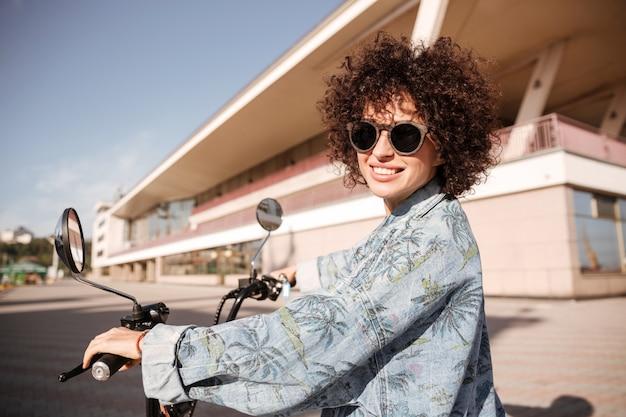 Vista lateral da jovem mulher encaracolada feliz em óculos de sol posando