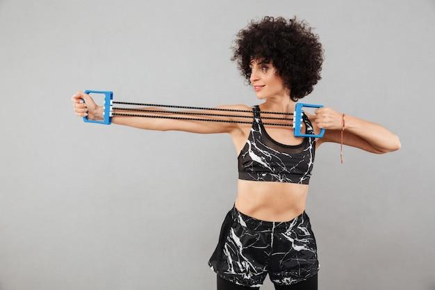 Vista lateral da jovem mulher fazendo exercício com mão expande