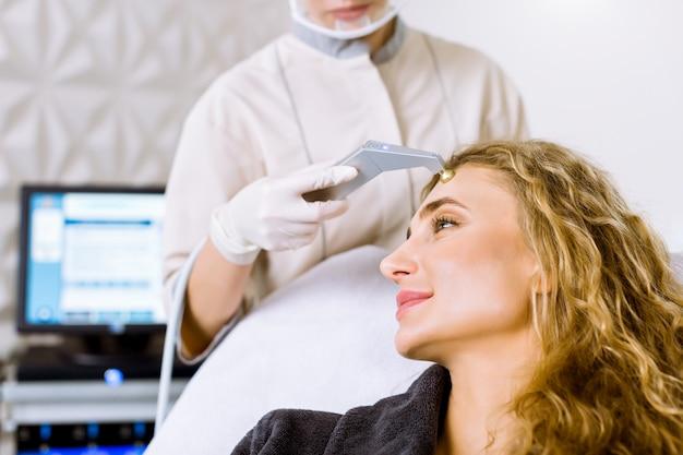 Vista lateral da jovem mulher loira recebendo massagem - microdermoabrasão na clínica cosmetológica moderna. esfoliação mecânica, polimento de diamantes.