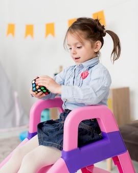 Vista lateral da jovem no slide segurando o cubo de rubik