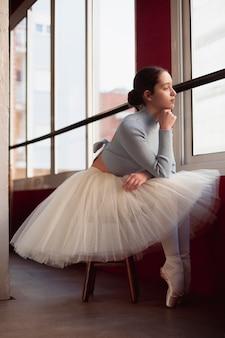 Vista lateral da linda bailarina em saia tutu posando ao lado da janela