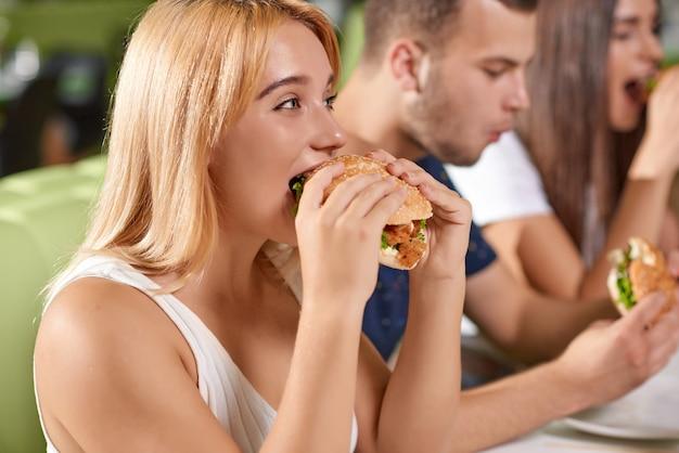 Vista lateral da loira com fome mordendo grande hambúrguer suculento