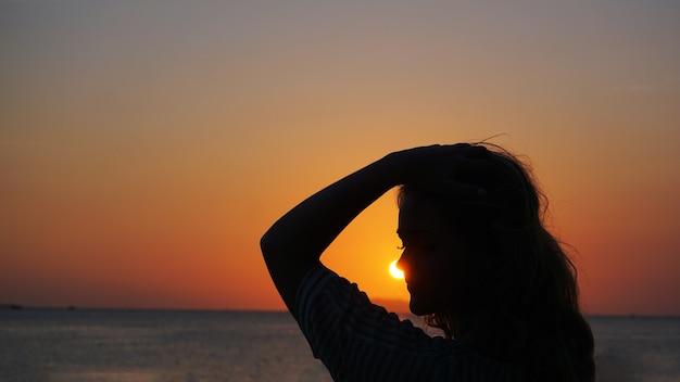 Vista lateral da luz de fundo de uma silhueta de mulher quente ao pôr do sol na frente do sol - praia turística ao pôr do sol