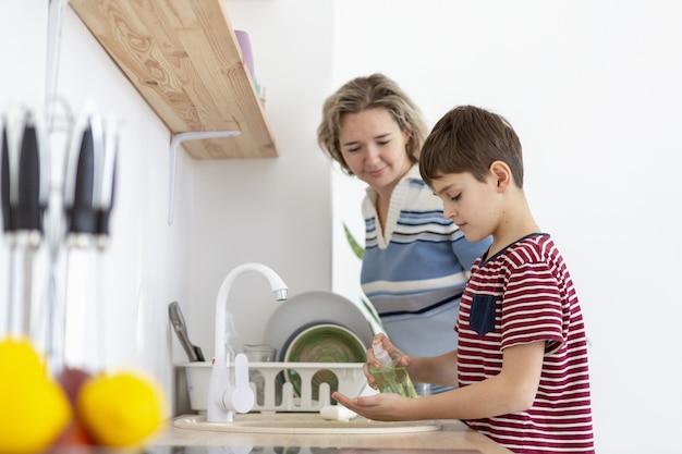 Vista lateral da mãe assistindo filho lavar as mãos
