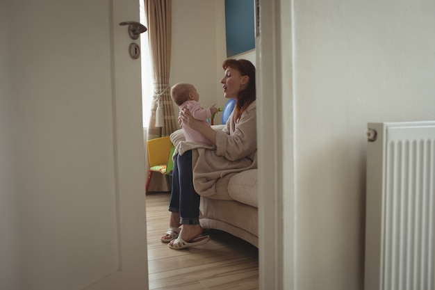 Vista lateral da mãe com o bebê sentado na cama