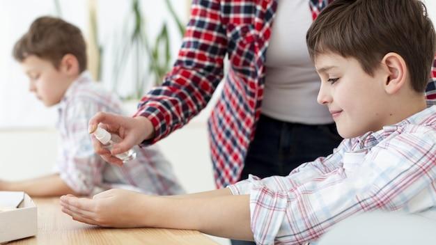 Vista lateral da mãe desinfetante nas mãos da criança