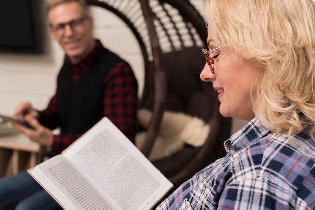 Vista lateral da mãe lendo livro com pai desfocado