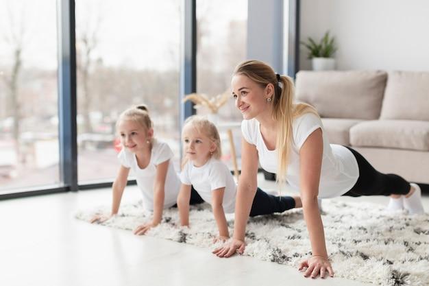 Vista lateral da mãe malhando com as filhas em casa