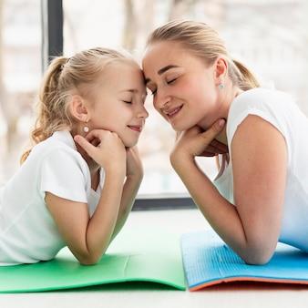 Vista lateral da mãe posando no tapete de ioga com a filha em casa
