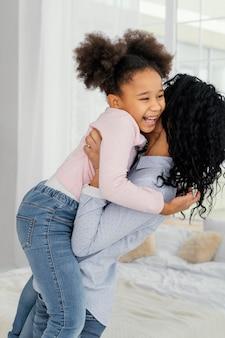 Vista lateral da mãe segurando sua filha sorridente