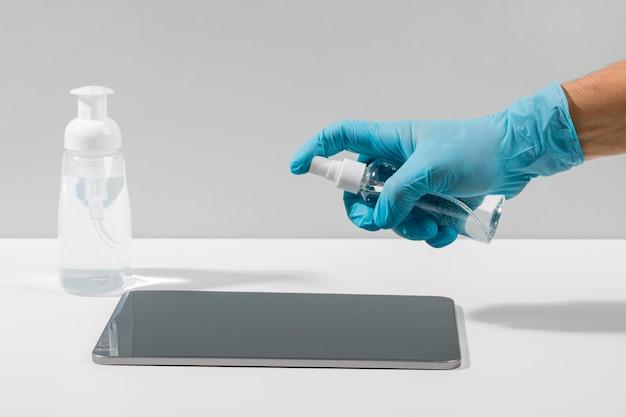 Vista lateral da mão com luva cirúrgica desinfetante comprimido