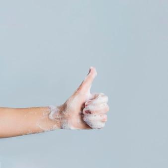 Vista lateral da mão com sabão desistindo polegares