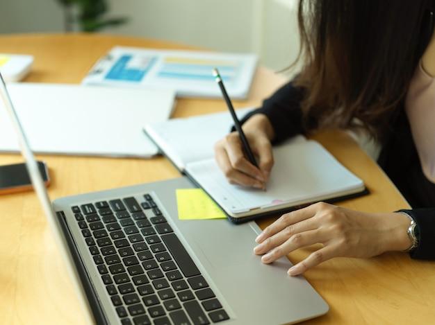 Vista lateral da mão da empresária escrevendo no livro de programação enquanto trabalha com o laptop na sala de escritório