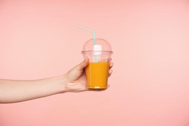 Vista lateral da mão da jovem sendo levantada, segurando o suco fresco com canudo nele, isolado sobre o fundo rosa. conceito de fotografia de alimentos e bebidas