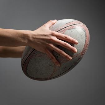 Vista lateral da mão de uma jogadora de rugby segurando uma bola