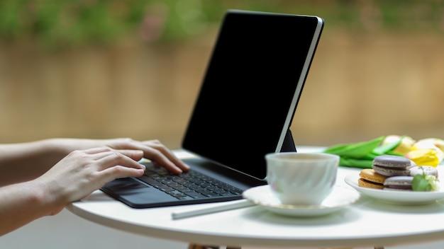 Vista lateral da mão digitando no teclado do tablet na mesa de centro com tae xícara e macarons coloridos franceses